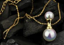 Pendente dorato dei gioielli con la perla sul fondo scuro del carbone Fotografia Stock Libera da Diritti