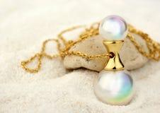 Pendente dorato dei gioielli con le perle sul fondo bianco della sabbia, co Immagine Stock