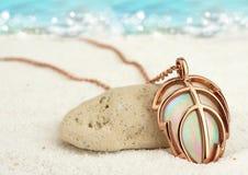Pendente dorato dei gioielli sulla spiaggia di sabbia di estate con il backgroun del mare Fotografie Stock