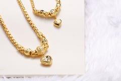 Pendente dorato del cuore, pizzo del collo, braccialetto dorato fotografie stock libere da diritti