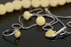 Pendente ed anello d'argento del primo piano con ambra su fondo degli orecchini e le perle sul bordo nero Fotografia Stock