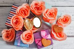 Pendentif vide ouvert entouré par des roses et des cadeaux Photos stock