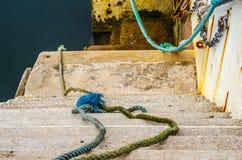 Pendiente abajo al océano en un puerto pesquero, cordones viejos y cuerdas Imágenes de archivo libres de regalías