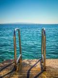 Pendiente de la verja del metal al mar Imagen de archivo libre de regalías