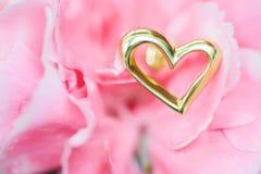 Pendiente del corazón en la flor rosada fotografía de archivo libre de regalías