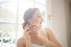 Pendiente que lleva de la novia hermosa mientras que hace una pausa la ventana Imagenes de archivo