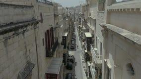 Pendiente vertical rápida, abejón que vuela la calle vieja hermosa estrecha, La Valeta, Malta Viejo, ventanas del vintage, balcon almacen de metraje de vídeo
