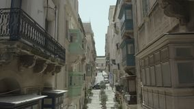 Pendiente vertical, vuelo del abejón a través de la calle vieja hermosa, La Valeta, Malta Viejo, ventanas del vintage, balcones - metrajes