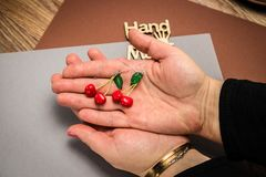 Pendientes de encargo hechos a mano de la arcilla del pol?mero de la cereza en fondo gris de la tela a mano fotos de archivo