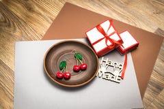 Pendientes de encargo hechos a mano de la arcilla del pol?mero de la cereza en la placa de madera fotos de archivo libres de regalías