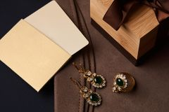 Pendientes de la joyería del diamante del ` s de las mujeres y un anillo con una esmeralda verde Foto de archivo libre de regalías