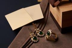 Pendientes de la joyería del diamante del ` s de las mujeres y un anillo con una esmeralda verde Fotos de archivo libres de regalías
