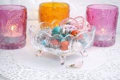 Pendientes de la joyería en un florero de cristal con las velas Imagenes de archivo