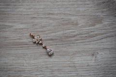 Pendientes de oro de la joyería en el fondo de madera imagen de archivo