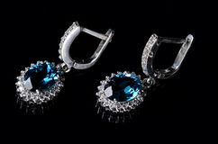 Pendientes de plata con el topacio azul en un fondo negro Fotografía de archivo