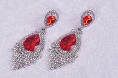 Pendientes de plata con los cristales rojos en un backg abstracto de la Navidad Imagen de archivo libre de regalías