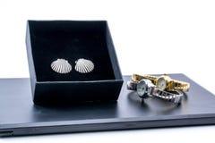 Pendientes de plata hermosos en una caja y dos relojes Fotos de archivo