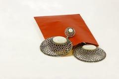 Pendientes de plata y sobre rojo Imagen de archivo