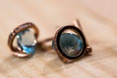 Pendientes del oro con los cristales azules claros Imagen de archivo libre de regalías