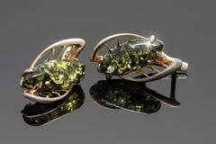 Pendientes del oro del primer con el ámbar báltico verde en el acrílico negro Imagen de archivo