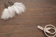 Pendientes delicados hermosos con las plumas en un fondo de madera Fotos de archivo
