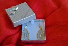 Pendientes hechos a mano de oro en una caja de regalo de plata Fotografía de archivo libre de regalías