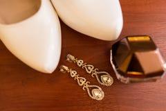 Pendientes nupciales con las piedras preciosas en el foco, perfume en la botella del oro, talones Fotografía de archivo libre de regalías