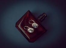 Pendientes y perfume del diamante Imágenes de archivo libres de regalías