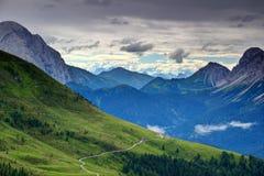 Pendii erbosi con la strada non asfaltata ed il chalet nelle alpi Italia di Carnic Fotografia Stock