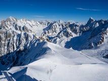 Pendio della neve con la montagna contro cielo blu ed i picchi ripidi delle alpi, Mont Blanc, Francia Fotografie Stock