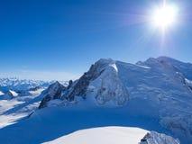 Pendio della neve con la montagna contro cielo blu ed i picchi ripidi delle alpi, Mont Blanc, Francia Fotografia Stock