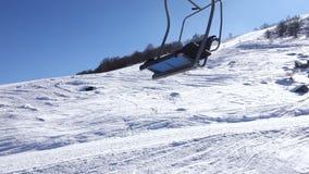 Pendio dello sci con corsa con gli sci della gente osservata dalla seggiovia muoventesi in un giorno di inverno soleggiato stock footage