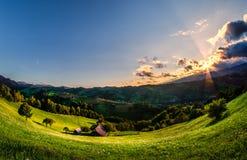 Pendio di collina e villaggio rumeni nell'ora legale, paesaggio della montagna della Transilvania in Romania Fotografia Stock