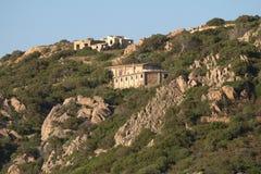 Pendio di montagna al tramonto, rovine. Baja Sardegna Immagini Stock