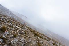Pendio di montagna della nebbia di viaggiatore con zaino e sacco a pelo Immagine Stock Libera da Diritti