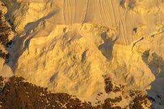 Pendio di montagna della neve in alpi al tramonto Fotografie Stock