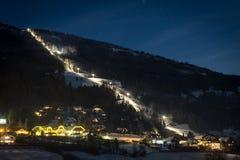 Pendio illuminato dello sci alle alpi austriache alla notte stellata Fotografie Stock Libere da Diritti