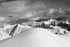 Pendio nevoso fuori-pista in bianco e nero e montagne nuvolose Immagini Stock