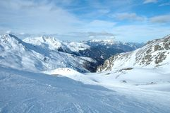 Pendio, picchi e valle dello sci in alpi nell'inverno Fotografia Stock Libera da Diritti