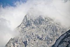 Pendio roccioso di una montagna coperta parzialmente da foschia nella gamma di Tennen nelle alpi austriache vicino alla città di  Immagini Stock Libere da Diritti