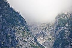 Pendio roccioso di una montagna coperta parzialmente da foschia nella gamma di Tennen nelle alpi austriache vicino alla città di  Immagine Stock Libera da Diritti