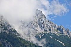 Pendio roccioso di una montagna coperta parzialmente da foschia nella gamma di Tennen nelle alpi austriache vicino alla città di  Immagine Stock