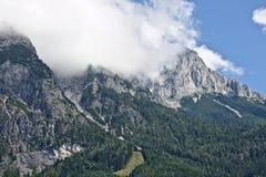 Pendio roccioso di una montagna coperta parzialmente da foschia nella gamma di Tennen nelle alpi austriache vicino alla città di  Fotografie Stock Libere da Diritti