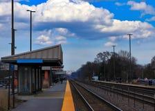 Pendlare på stationsplattformen efter det Metra drevet passerar till och med en station för drev för Chicago förort` s royaltyfria foton
