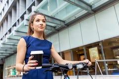 Pendling för ung kvinna på cykeln arkivfoton