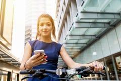 Pendling för ung kvinna på cykeln fotografering för bildbyråer