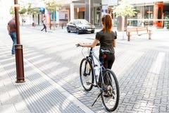 Pendling för ung kvinna på cykeln arkivfoto