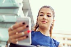 Pendling för ung kvinna på cykeln som rymmer en mobil arkivfoton