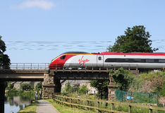 Pendolino electric train crossing Lancaster canal. Front car of Virgin liveried electric multiple unit (number 390 141) Pendolino train as it crosses a bridge Stock Image