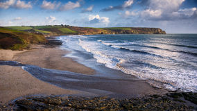 Pendower Beach. Cornwall, United Kingdom. Tide going out, sun setting over the sea Royalty Free Stock Images